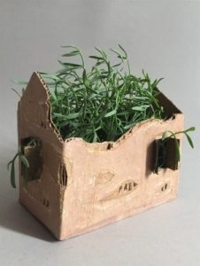 Cardboard box made to look like a house with mistletoe inside
