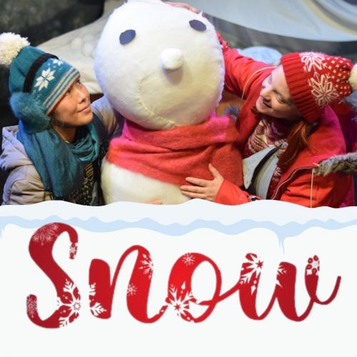 Actors in woolly hats and coats with a giant snowman